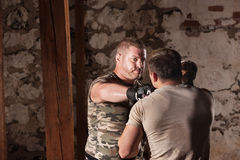 Reverse Punch Hits Opponent. MMA fighter throws a reverse punch at partner Stock Photography