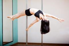 Reverse superwoman in a pole. Pretty Hispanic girl holding the reverse superwoman pose in a pole fitness class Stock Photography