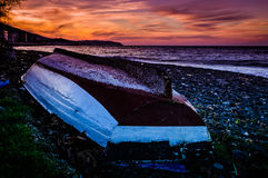 Reversed Fishermen Rowboat On Sunset Shore Stock Photo