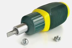 Reversible screwdriver and two screws. On a light background Royalty Free Stock Image
