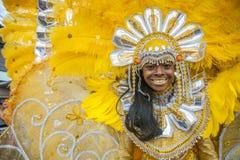 Revestido en una mascarada brillante del amarillo y del oro una mujer sonriente joven disfruta del desfile de carnaval del ` s de Fotos de archivo