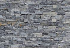 Revestimento cinzento da parede de pedra feito das tiras e dos blocos quadrados empilhados Fundo e textura imagens de stock royalty free