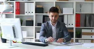 Revestimento cinzento do homem novo que senta-se na tabela no escritório branco e em originais de oferecimento
