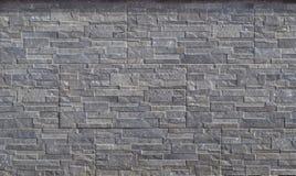 Revestimento da parede de pedra feito das listras cinzentas horizontais gravadas da rocha empilhadas nos painéis imagem de stock royalty free
