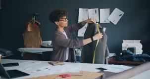 Revestimento de medição do desenhista de roupa da jovem mulher com notas da escrita da medida-fita video estoque