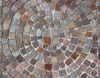 Revestimento de pedra exterior dos cubos do pórfiro feitos com um projeto redondo, com círculos que se transforme partir maior do imagem de stock