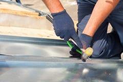 Revestimento do trabalhador do construtor do Roofer que dobra uma folha de metal usando o malho de borracha Fotos de Stock