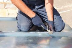 Revestimento do trabalhador do construtor do Roofer que dobra uma folha de metal usando o malho de borracha Imagens de Stock Royalty Free