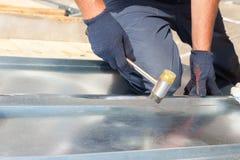 Revestimento do trabalhador do construtor do Roofer que dobra uma folha de metal usando o malho de borracha Fotos de Stock Royalty Free