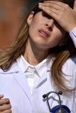 Revestimento fêmea do laboratório de With Headache Wearing do médico fotos de stock royalty free
