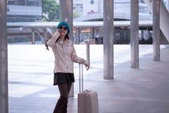 Revestimento vestindo da camiseta da mulher asiática do curso, chapéu azul do fio com lugg Imagens de Stock Royalty Free