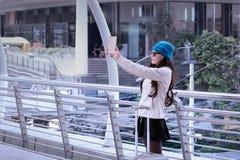 Revestimento vestindo da camiseta da mulher asiática do curso, chapéu azul do fio com lugg Fotos de Stock