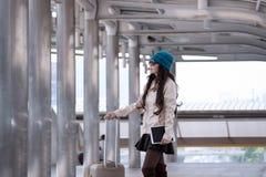 Revestimento vestindo da camiseta da mulher asiática do curso, chapéu azul do fio e posse Imagem de Stock Royalty Free