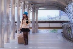 Revestimento vestindo da camiseta da mulher asiática do curso, chapéu azul do fio e posse Imagens de Stock Royalty Free