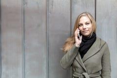 Revestimento vestindo da jovem mulher usando a parede do metal do smartphone Imagem de Stock Royalty Free