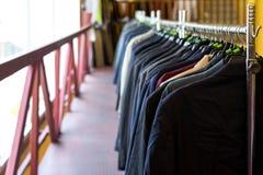 Revestimentos, ternos e camisas pendurando na cremalheira foto de stock royalty free