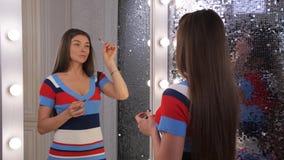 Revestimientos del tiempo Una mujer joven hermosa pinta sus cejas, da vuelta en una cámara y sonrisas 4K almacen de video