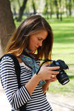 Review. The girl-photographer in spring park Stock Images