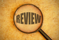 Review. Magnifying glass focused on the word review royalty free stock image