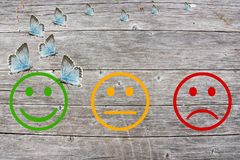 Review classification with happy and angry faces on wooden background.  Royalty Free Stock Photography
