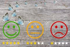 Review classification with happy and angry faces on wooden background and stars.  stock image