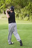 Review Golf Swing. Review of man completing golf swing on fairway stock photos