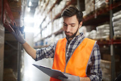 Review of goods. Serious warehouse worker checking up goods on shelves Stock Photography