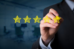 Review increase rating. Review, increase rating, performance and classification concept. Businessman draw five yellow stars to increase rating of his company royalty free stock photos