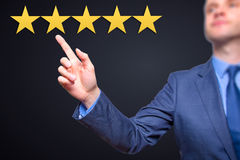 Review, increase rating or ranking, evaluation and classification concept. Businessman pointing on five yellow stars to increase stock image
