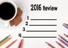 2016 review list. White desk with and a cup of coffee Royalty Free Stock Images