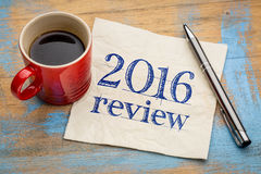 2016 review on napkin. 2016 review text on a napkin with coffee against grunge wood desk royalty free stock photo