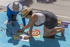 Lake Worth, Florida, USA Fab 23-24, 2019 25Th Annual Street Painting Fest. After a review of the next step, they continue to blend in more colors with chalk on stock photos