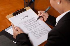 Review Resume. A Woman looking over a resume with a pen in her hand Stock Photography