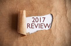 2017 review. Torn piece of scroll uncovering 2017 review Stock Photography