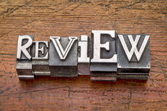 Review word in metal type. Review word in mixed vintage metal type printing blocks over grunge wood stock image