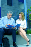 Reviewing Business Papers-2. Two casually dressed business people look over a folder with documents regarding an important project on which they are working Stock Photo