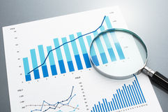 Reviewing business report. Looking at growth chart with magnifyi Royalty Free Stock Image