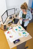 Reviewing conceptual design sketches. Designer, standing behind her desk in a design studio, reviewing a large variety of conceptual design drawings and sketches stock image
