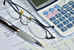 Reviewing the financial report of a company. Reviewing a company's financial report and balance sheet Stock Photo