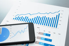 Reviewing financial report. Document and smart phone. Royalty Free Stock Images
