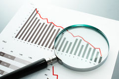 Reviewing financial report. Looking at decrease chart with magni. Document, chart and magnifying glass on gray reflection background Royalty Free Stock Photography