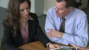Reviewing marketing materials with client. Reviewing marketing materials with male client stock footage