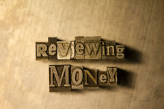 "Reviewing money - Metal letterpress lettering sign. Lead metal ""Reviewing money"" typography text on wooden background Royalty Free Stock Photos"