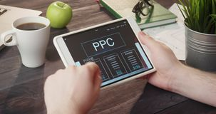 Reviewing PPC info using digital tablet at desk stock video footage