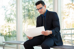 Reviewing some documents. Young businessman sitting on a bench and reviewing some documents at work Royalty Free Stock Image