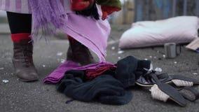 Revirar desabrigado na roupa dispersada na rua Fim acima video estoque