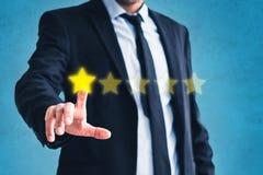 A revisão má, homem de negócios dá uma de cinco estrelas - feedback negativo do traje imagem de stock