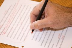 Revise Close. A hand makes revisions to a document using a red pen Stock Photo