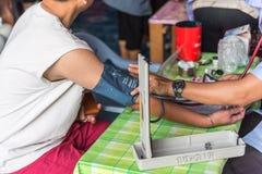 Revisión médica tailandesa del hombre por el indicador de presión Fotos de archivo libres de regalías