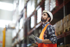 Revision of goods. Worker with touchpad revising goods in storehouse royalty free stock photos